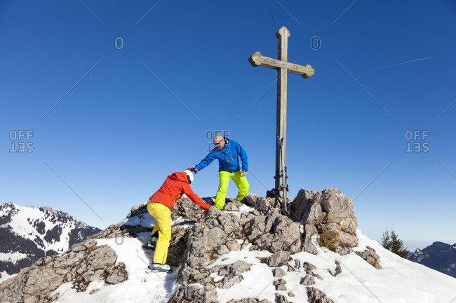Ski holiday, Two skiers arriving mountain peak, Sudelfeld, Bavaria, Germany