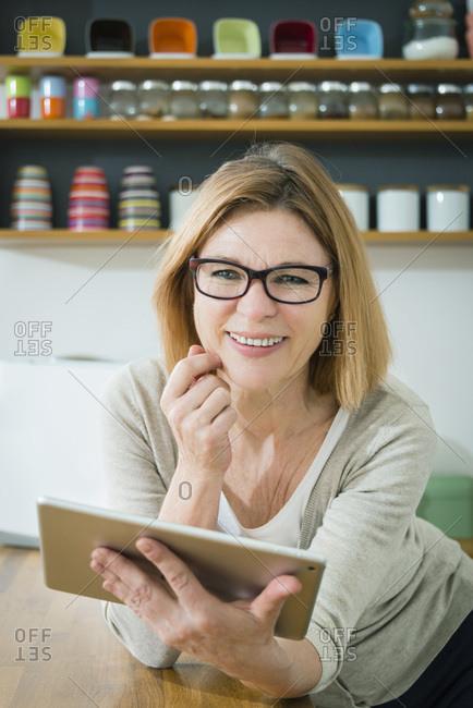 Senior woman in kitchen using tablet pc, portrait