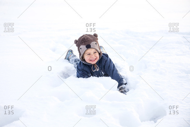 Little boy with bear costume playing in snow