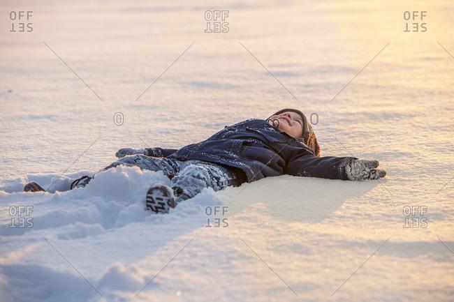 Little boy lying on back in snow
