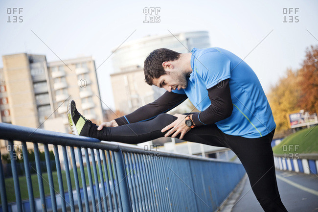 Male runner stretching and warming up in city
