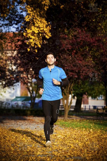 Male runner jogging in autumn park