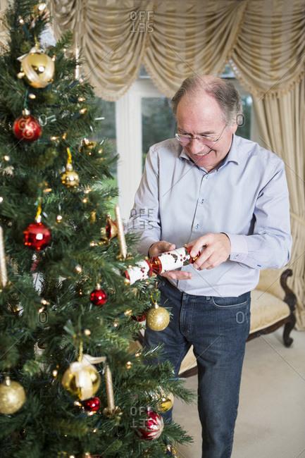 Senior man opening Christmas cracker by Christmas tree