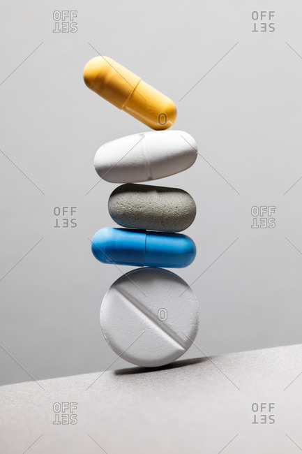 Pills of different sizes and shapes stacked on a slanted background