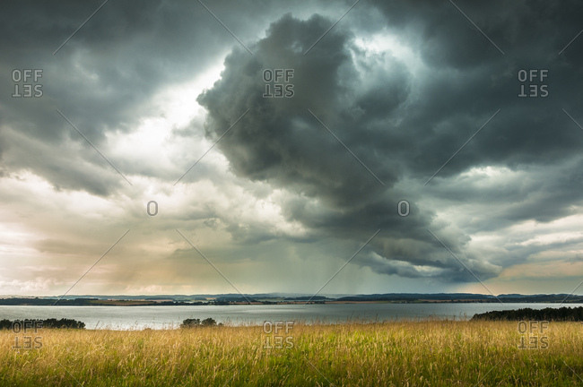 Grass landscape, view of Bodden, stormy weather, Monchgut Nature Reserve, Monchgut Peninsula, Southeast Rugen Biosphere Reserve, Rugen, Mecklenburg-Vorpommern, Germany, Europe