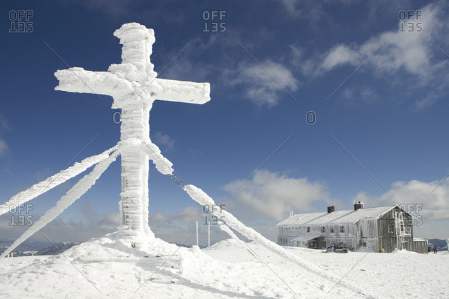 Snow covered cross and the Alois Gunther mountain hut on top of the mountain Stuhleck Styria Austria