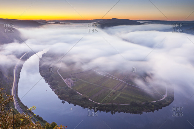 View of the bend in the Moselle at dawn and sunrise with fog as seen from the Calmont ridge, Bremm, Rhineland-Palatinate, Germany, Europe