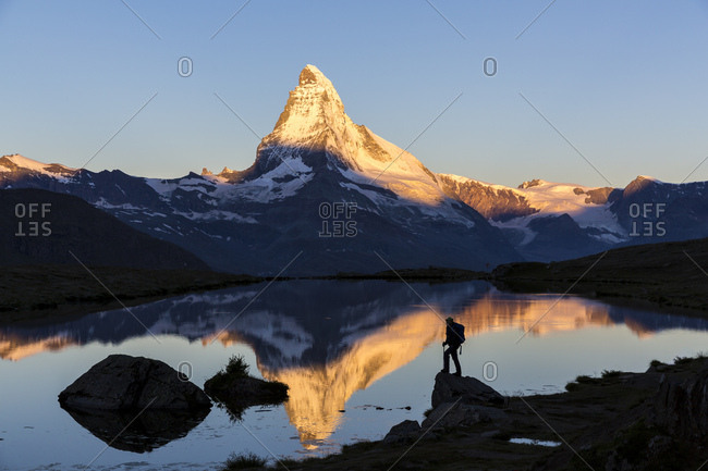 August 18, 2014: First sunlight on the Matterhorn, with reflection in Stellisee lake, with a person, Zermatt, Canton of Valais, Switzerland, Europe