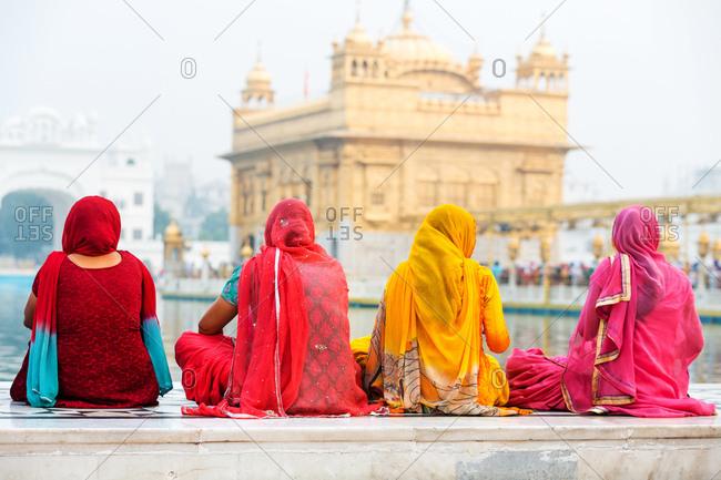 Sikh women pilgrims sitting in front of the Harmandir Sahib or Golden Temple, Amritsar, Punjab, India, Asia