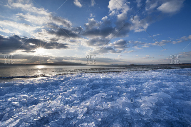 Sunlight with moody clouds, stacked ice floes on the shore of Reichenau Island, Baden-Wuerttemberg, Germany, Europe