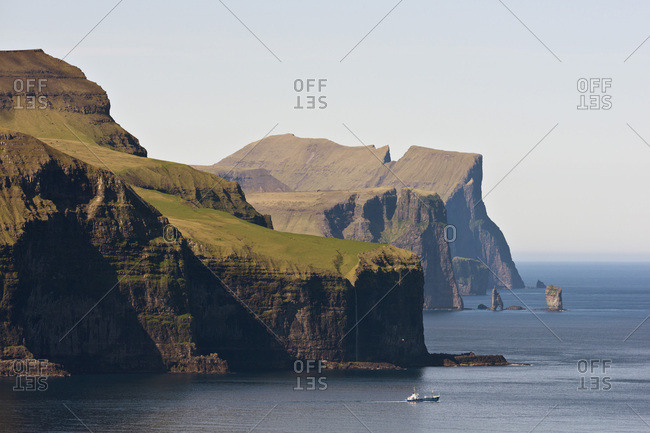 Fishing boat in front of Eysturoy, the basalt columns Risin and Kellingin at the back, Kalsoy, Faroe Islands, Denmark, Europe