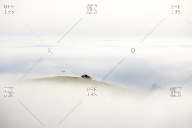 Foggy view of Bisberg with summit cross, Hegau, Baden-Wurttemberg, Germany, Europe