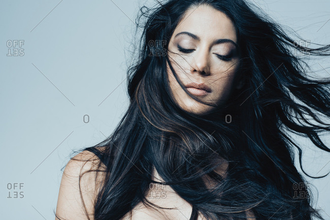 Beautiful young woman with long black hair against blue background