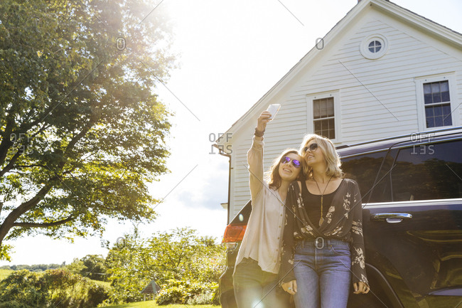 Happy young female friends taking selfie using mobile phone against car outside house