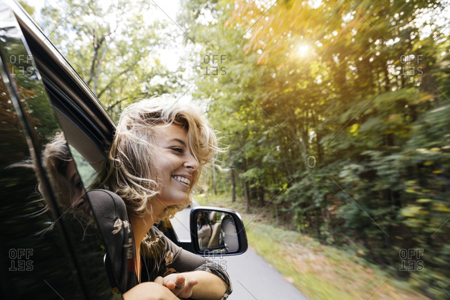 Beautiful young woman looking out of car window during road trip in countryside