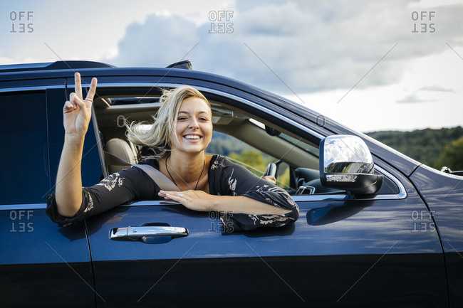 Portrait of smiling young woman gesturing peace sign while looking out of car window during road trip