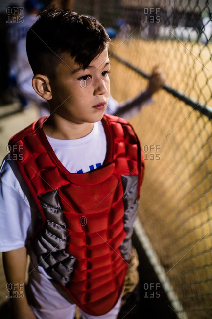 Boy in dugout wearing catcher gear