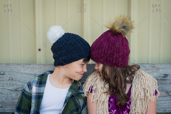 Brother and sister face to face wearing knit hats
