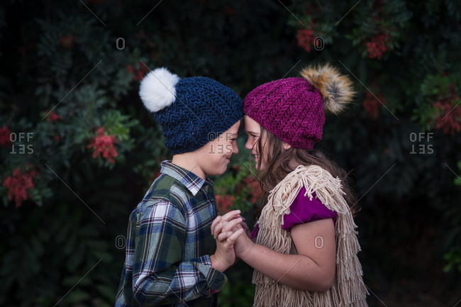 Brother and sister face to face while holding hands