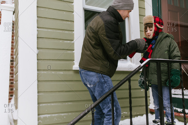 Older brother adjusts younger brother's scarf outside