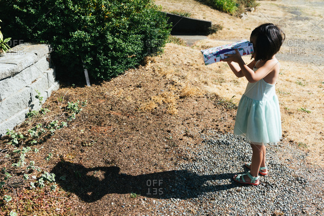 Young girl looks through handmade eclipse viewer