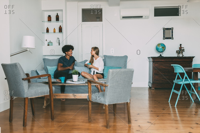 Happy young interracial couple relaxed at home sitting on the sofa talking and having coffee