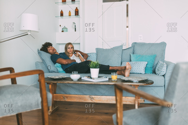 Happy young interracial couple relaxed at home lying down on the sofa watching tv
