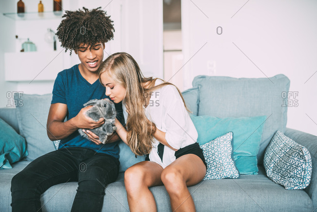 Happy young in love interracial couple relaxed at home caressing a little bunny