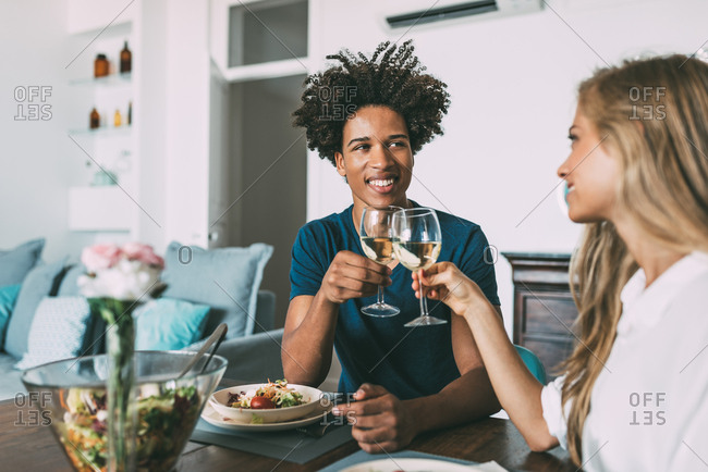 Happy young in love interracial couple celebrating with a romantic lunch on Valentine's day at home