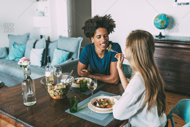 Happy young in love interracial couple celebrating with a romantic lunch on Valentine\'s day at home