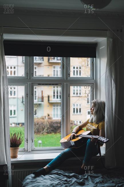 Musician sitting at window