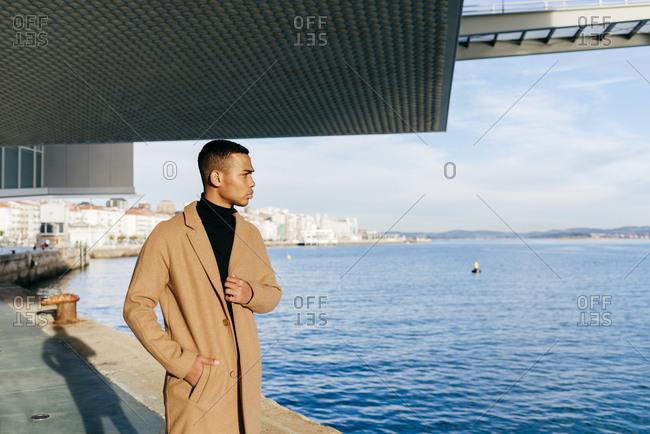Black man in stylish coat at embankment