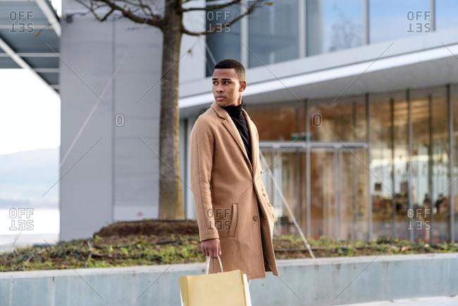 Man with shopping bag walking in street