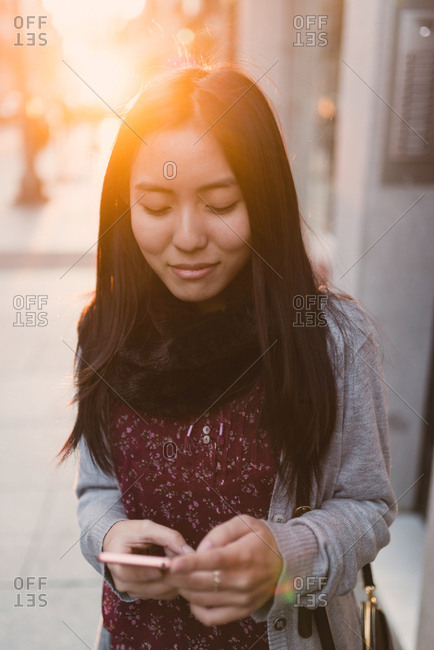 Young pretty Asian woman standing in back lit and browsing smartphone on city street