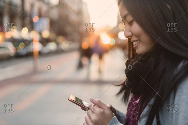 Asian woman browsing smartphone on street