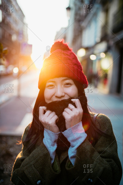 Cheerful young Asian woman looking at camera and posing in back lit on city street