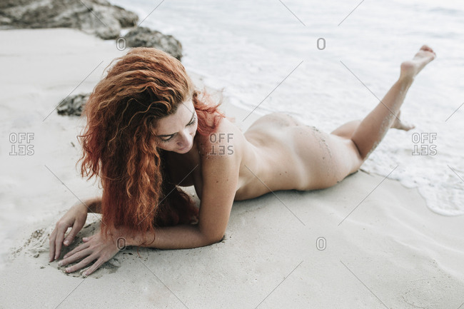 Attractive naked redhead woman lying and posing in ocean waves on sandy coast