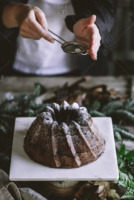Crop person standing near table and sprinkling chocolate cake with powdered sugar