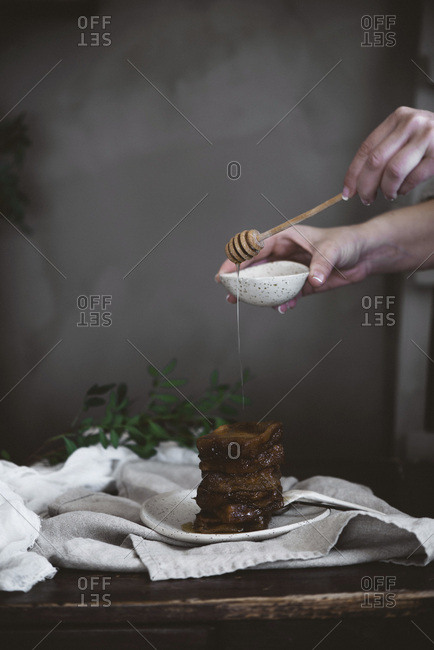 Hands of unrecognizable person pouring honey on chocolate dessert with wooden spoon