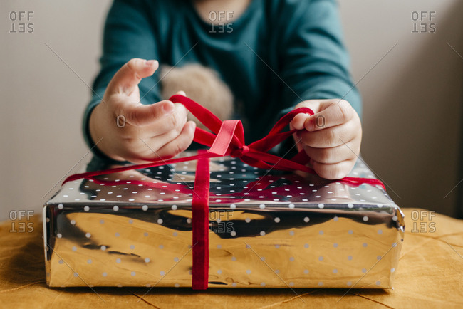 Crop child sitting at table and tying red ribbon on gift box wrapped in shiny paper