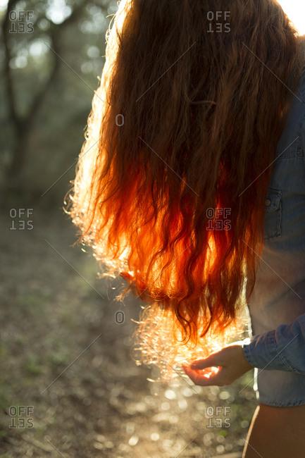 Pretty unrecognizable redhead woman posing in sunny forest