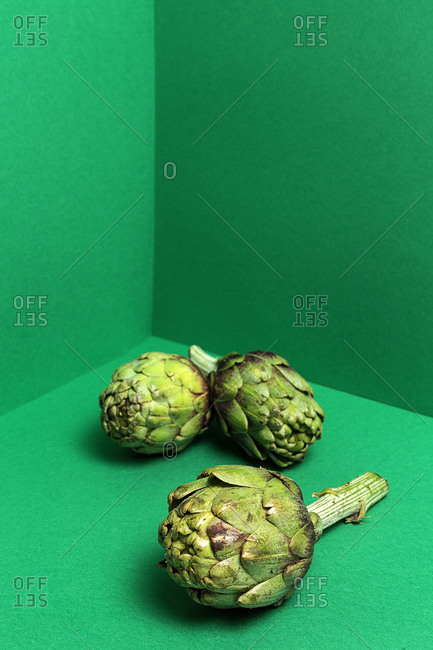 Three fresh whole artichokes on bright green background
