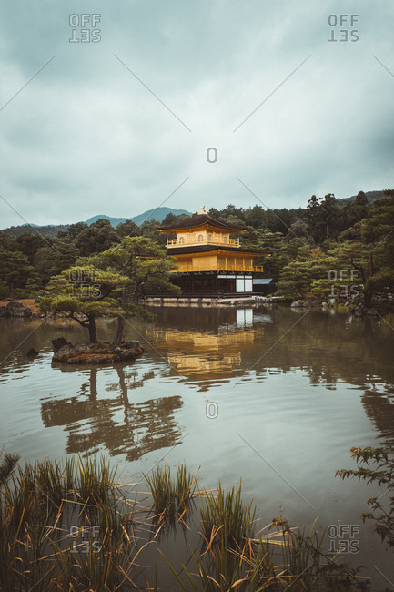 Picturesque view of pretty Asian house standing on shore of calm lake