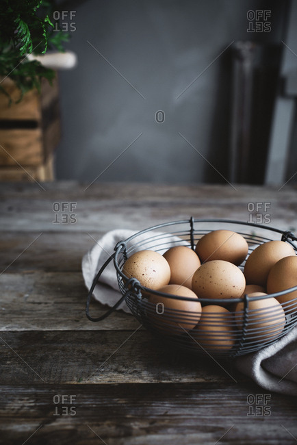 Bunch of chicken eggs lying in net bowl on timber tabletop