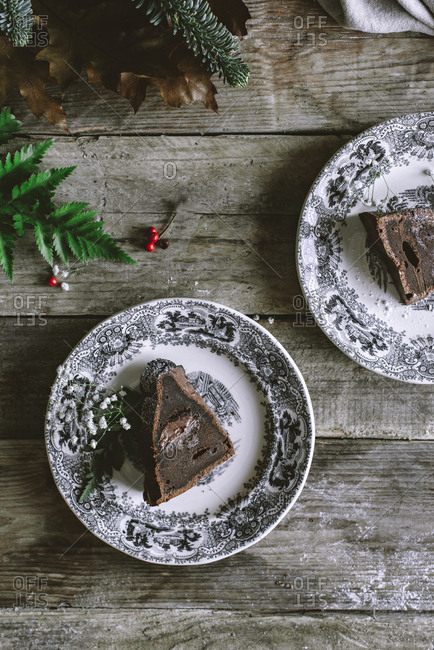Plate with piece of delicious chocolate cake standing on wooden tabletop