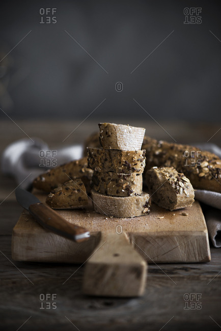 Slices of fresh cut bread lying near knife on wooden cutting board