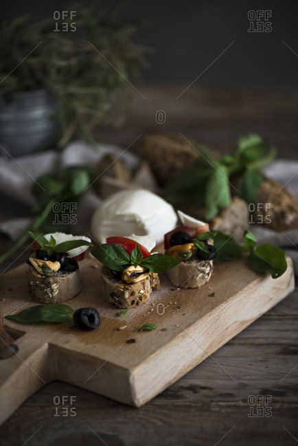 Three delicious canapes lying on wooden cutting board near cheese