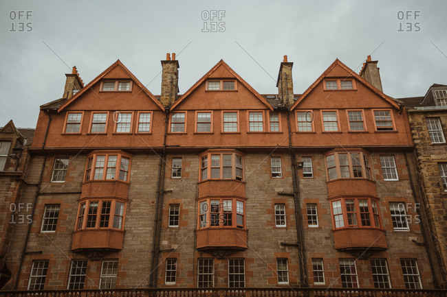 Facade of beautiful monumental building made of stone and brick under gloomy sky