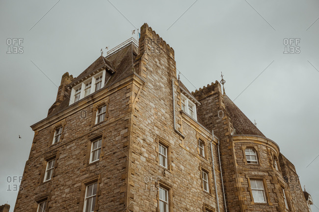 From below view of beautiful old building made with stone and brick