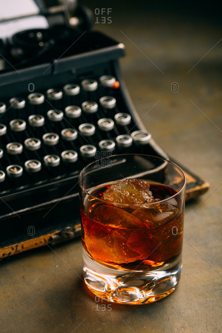 Glass of whiskey and a retro typewriter